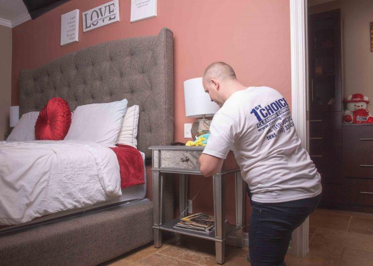 man dusting nightstand