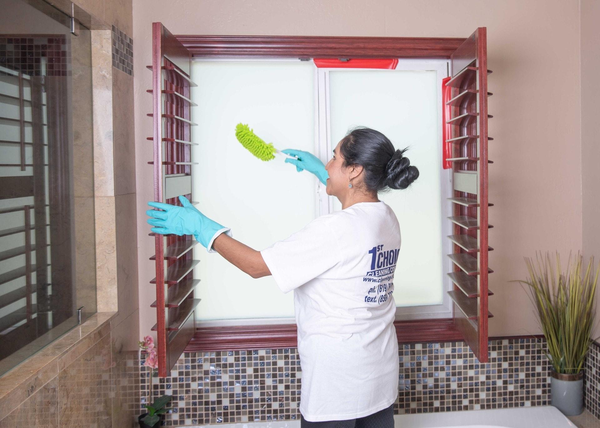 women dusting blinds in a bathroom